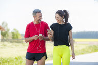 Couple using smartphones during workout - DIGF04365