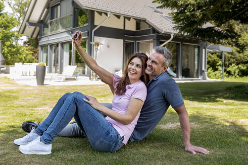 Happy couple sitting in garden of their home taking a selfie - DIGF04368