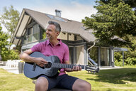 Smiling mature man sitting in garden of his home playing guitar - DIGF04371