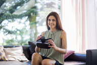 Smiling woman sitting on couch at home holding VR glasses - DIGF04380