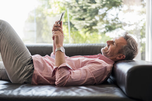 Smiling mature man lying on couch at home using a cell phone - DIGF04386