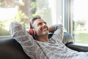 Happy mature man lying on couch at home wearing headphones - DIGF04389