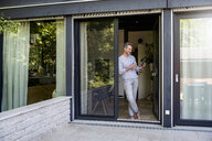 Smiling mature standing at French door at home using a tablet - DIGF04395