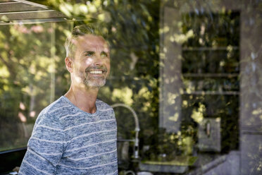 Portrait of smiling mature man behind windowpane at home - DIGF04398