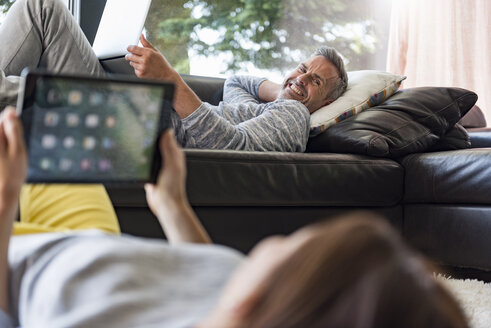 Couple relaxing in living room at home using tablet and laptop - DIGF04401