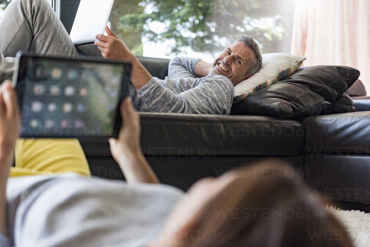 Couple relaxing in living room at home using tablet and laptop - DIGF04401 - Daniel Ingold/Westend61