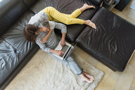 Couple on couch at home sharing a laptop - DIGF04404