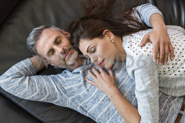 Relaxed couple lying on couch at home - DIGF04407 - Daniel Ingold/Westend61