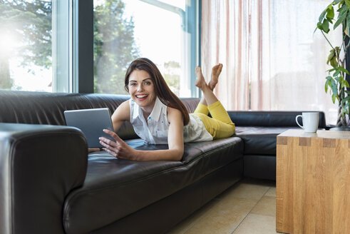 Portrait of happy woman lying on couch at home using a tablet - DIGF04410