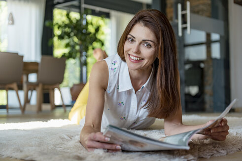 Portrait of happy woman lying on carpet at home reading a magazine - DIGF04413