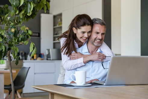 Happy couple at table at home sharing a laptop - DIGF04425