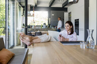 Relaxed woman at home using a laptop at table with man in background - DIGF04434