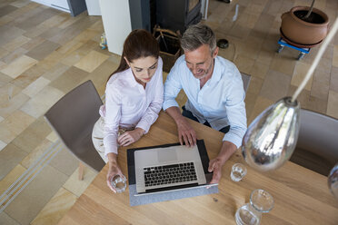 Couple sitting at table at home sharing a laptop - DIGF04437