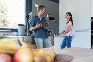 Couple in kitchen at home cooking and using a tablet - DIGF04440