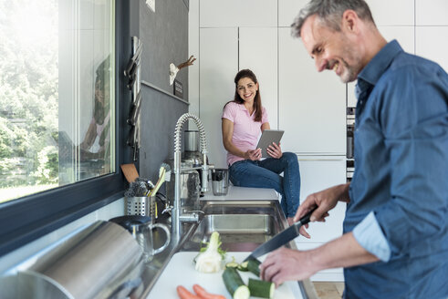 Happy couple in kitchen at home cooking and using a tablet - DIGF04443