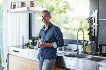 Smiling mature man at home in kitchen with cup of coffee - DIGF04449