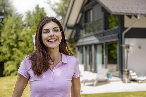 Portrait of happy woman in garden of her home - DIGF04464