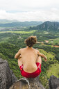 Laos, Vang Vieng, young man on top of rocks overlooking landscape of rice fields - AFVF00514