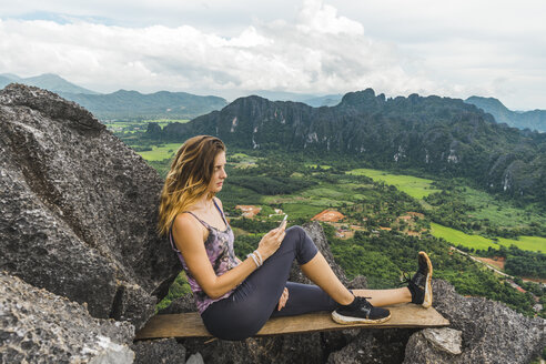 Laos, Vang Vieng, young woman on top of rocks using cell phone - AFVF00520