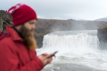 Iceland, North of Iceland, young man using smartphone, waterfall in the background - AFVF00535