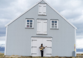 Iceland, young man playing guitar, wooden house - AFVF00538