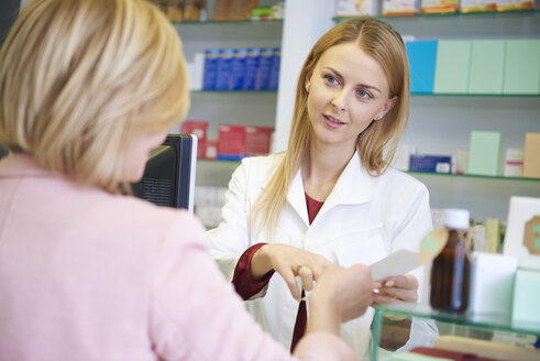 Portrait of pharmacist advising woman in pharmacy - ABIF00393