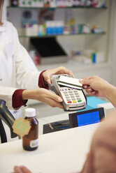 Customer paying cashless with credit card in a pharmacy - ABIF00399