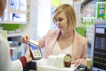 Portrait of woman paying cashless with credit card in a pharmacy - ABIF00405