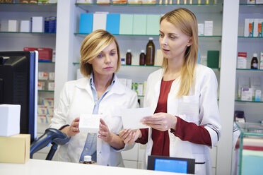Two pharmacists working together in pharmacy - ABIF00408