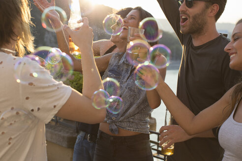 Adult friends playing with floating bubbles at roof terrace party - ISF02199