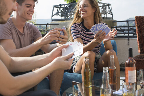 Adult friends playing card games at roof terrace party - ISF02232