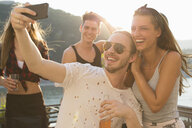 Young man taking selfie with female friend at waterfront roof terrace party, Budapest, Hungary - ISF02235