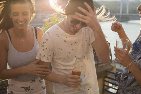 Young couple at windy waterfront roof terrace party, Budapest, Hungary - ISF02238