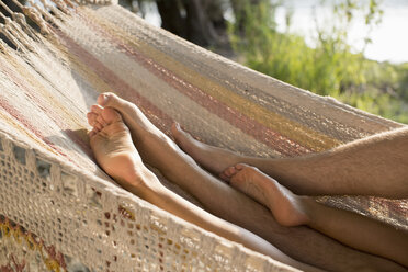 Couple relaxing in hammock, view of legs - ISF02277