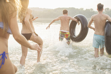 Friends having fun with inflatable ring in river - ISF02295