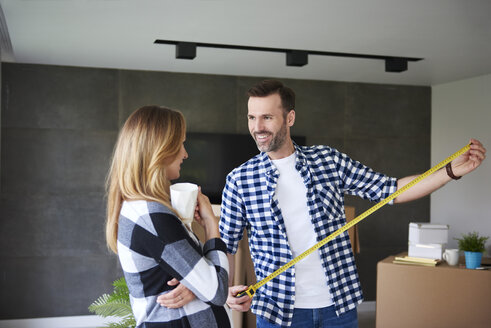Couple moving into new flat measuring with tape measure - ABIF00414