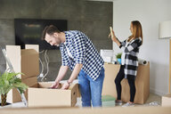 Couple moving into new flat unpacking cardboard box - ABIF00417