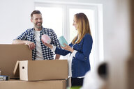 Couple moving into new flat packing cardboard boxes - ABIF00426
