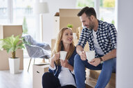 Man and pregnant woman moving into new flat having a coffee break - ABIF00429