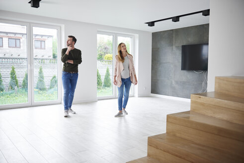 Couple looking around in empty flat - ABIF00435