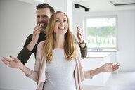 Man surprising woman in empty flat - ABIF00438