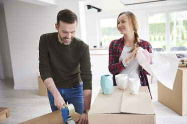 Couple moving house packing and taping cardboard boxes - ABIF00444