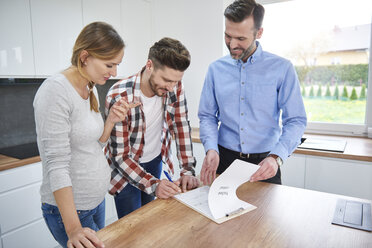 Couple with real estate agent signing contract in kitchen of new apartment - ABIF00450