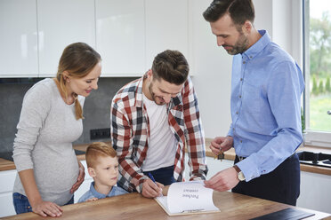 Family with real estate agent signing contract in kitchen of new apartment - ABIF00453