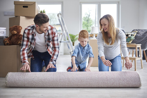 Family unrolling a carpet in new flat - ABIF00462