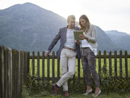 Man and woman sharing tablet in rural landscape - CVF00584