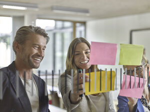 Happy colleagues discussing with sticky notes at glass pane - CVF00587