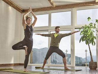 Couple practicing yoga in a room with panorama window - CVF00596
