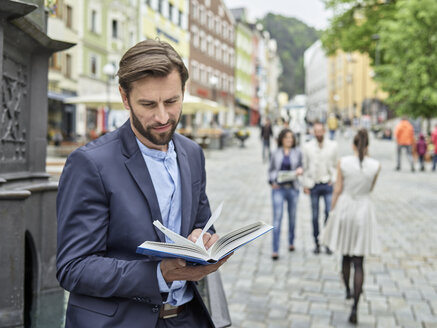 Businessman reading book in the city - CVF00605