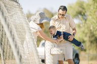 Family at playground,  father holding young son over water fountain - ISF02384
